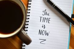 `The time is now` hand-lettered in notebook. On wooden desk with pen and cup of coffee royalty free stock photos