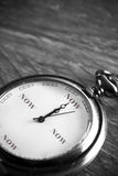 Time is now. Pocket watch on a vintage table showing the time now stock photo