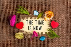 The time is now written in hole on the burlap. The is now written in hole on the burlap with dried flowers and wooden red heart and blue stone royalty free stock image