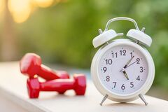 Time 5 oclock morning for exercising alarm clock and dumbbells on green natural background outside  sport and workout concept