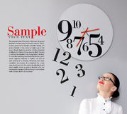 Time in office. Business Woman under the clock. Concept Royalty Free Stock Image