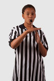 Time out. Young african american girl wearing a black and white striped referee top blowing a whistle stock photos