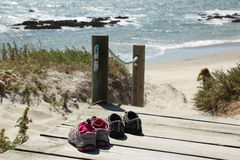 Time out. Kids shoes left on the pathway of a nice quiet beach Stock Image