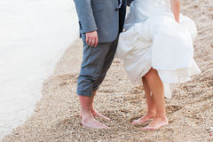 Time out. Feet of the bride and groom being photographed on the beach Stock Photos
