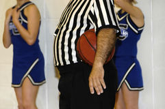 Time Out. Referee waits as coaches use a time out.  Ref holds ball under his arm, arm hangs straight down.  Two cheerleaders in blue uniforms are against a white Royalty Free Stock Image