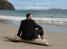 Time Out at the Beach. Man in a business suit relaxing on a piece of drift wood at the beach Royalty Free Stock Image