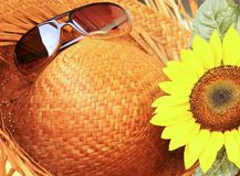 Time out. Closeup of a straw hat with sunglasses and a sunflower on a sunny day Royalty Free Stock Photography