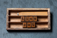 Time out concept. Vintage box, wooden cubes with old style letters, retro style pencil. Gray stone textured background. Macro, up view, soft focus photo Stock Photo