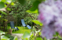 Time out in the garden - lounger chairs on the terrace. Royalty Free Stock Images