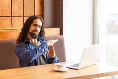 Time-out! Portret van de ernstige knappe jonge volwassen mens freelancer in toevallige stijlzitting in koffie en het spreken met  stock fotografie