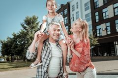 Nice happy girl sitting on her dads shoulders. Time with parents. Nice happy girl smiling while sitting on her dads shoulders stock photography