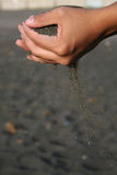 Time passing. Black sand falling from hands symbolizing time passing Stock Photography