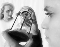 Time Passing. Black and white photo of a teenage girl looking at an hourglass, and an older version of the teenage girl looking at the hourglass from the Royalty Free Stock Image