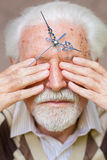 Time passing. Clock hands placed on elderly mans forehead Stock Image