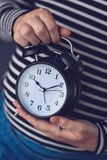 Time is passing, female hand with vintage alarm clock. Time is passing, female hand holding stylish black vintage alarm clock, selective focus Royalty Free Stock Photography