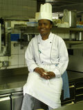 Time for a pause. A black female chef sitting in the kitchen during a pause royalty free stock photo