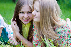 Time for picnic: 2 beautiful girls friends young women lying on grass happy smile having fun & one looking at camera. Tow best friends beautiful girls lying Stock Image
