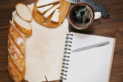 Time planning while coffee break with bread and cheese. Planning the day, finances or diet during the coffee break with fresh bread and refined cheese on the royalty free stock photos