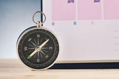 Compass and calendar on wooden desk over gently lit dark background. Time Planning and direction concept, compass and calendar on wooden desk over gently lit stock photos