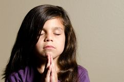 Time for prayer. A little girl praying with her eyes closed Royalty Free Stock Photography