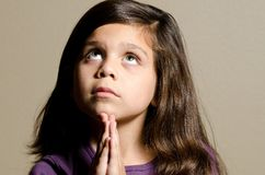 Time for prayer. A little girl praying while she looks up Stock Images