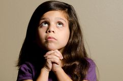 Time for prayer. A little girl praying while she looks up Stock Photo