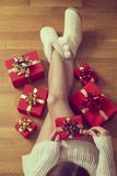 Time for presents. Detail of naked female legs with lots of nicely wrapped presents all around Royalty Free Stock Photos