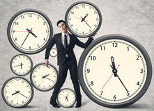Time pressure concept. Asian business man with many clocks Stock Images