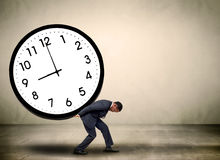 Time pressure concept. Businessman buckled under time pressure with a clock face.  Time management concept Stock Images