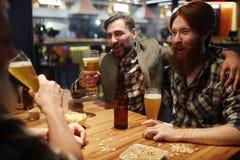 Time in pub. Joyful men having nice time in pub Royalty Free Stock Images