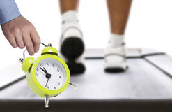 Time for recreation. Alarm clock and close up of man running on treadmill Stock Photos