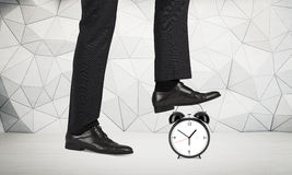 Time reduction concept. Witt businessman foot stepping on alarm clock. Patterned wall in the background Royalty Free Stock Photography