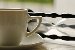 Time for relax. Coffee cup and hourglass lying in the background - symbolising time for relax Royalty Free Stock Photography