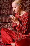 Time for relaxation with cup of tea. Beautiful blond girl with cup of tea in oriental interior Stock Images