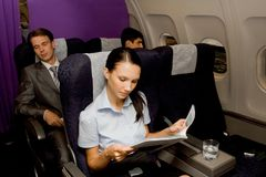 Time of rest. Image of pretty girl reading magazine in airplane with sleeping men behind Royalty Free Stock Images