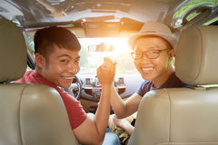It is Time for Road Trip. Group portrait of joyful Vietnamese friends looking at camera with wide smiles and giving high five while sitting in car ready for Royalty Free Stock Photo