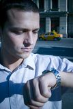 Time is running. A young businessman with a deadline rushed for time, checking his watch Royalty Free Stock Image