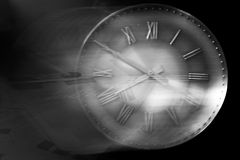 Time is running away in a heap of paperwork. Retro clock against a black background with motion blur filled with paperwork showing how time is lost to work Royalty Free Stock Image