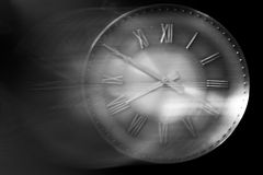 Time is running away. Retro clock against a black background with motion blur showing how time flies Stock Image