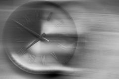 Time is running away. Retro clock against a wooden background with motion blur showing how time flies Royalty Free Stock Photography