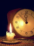 Time Running Out. A low-burning candle illuminating an old clock that is showing a few minutes to midnight Stock Photography