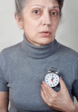 Time is running out. Portrait of an elderly woman holding a clock near the heart concept of time is running out Royalty Free Stock Image