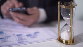 Time running out with sand in hourglass, defocused man using smartphone for work stock video