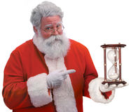 Time is Running Out for Shopping. Santa on a white background pointing to an hour glass indicating that Christmas is fast approaching Stock Photos