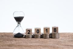 Time running year 2018 financial or investment concept with hour. Glass or sandglass and cube block number 2018 on stack of coins put on wooden table with white Stock Photo
