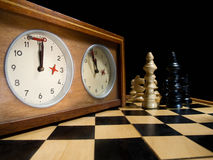 Time's up!. Old chess clock on the chessboard with figures ,flag in position which indicates  running out of time Royalty Free Stock Photography