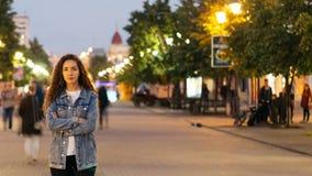 Time-schackningsperiod av den olyckliga flickan som bara sent står på den härliga fot- gatan i aftonen och ser kameran när lager videofilmer