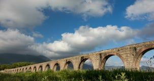 Time-schackningsperiod av moln nära akvedukten och bergsikterna arkivfilmer