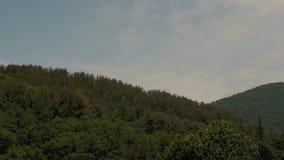 Time-schackningsperiod sommar Gröna bergmaxima mot en bakgrund av vitmoln och en blå himmel Resa till bergen stock video