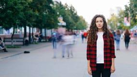 Time-schackningsperiod stående av den confedent unga kvinnan som bara står i gatan på sommardag och ser kameran medan arkivfilmer
